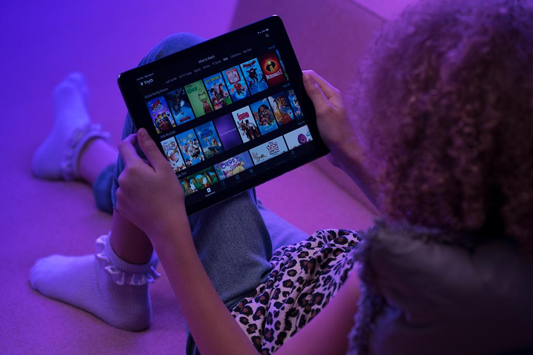 Image of an ipad being held by a girl showing TiVo app