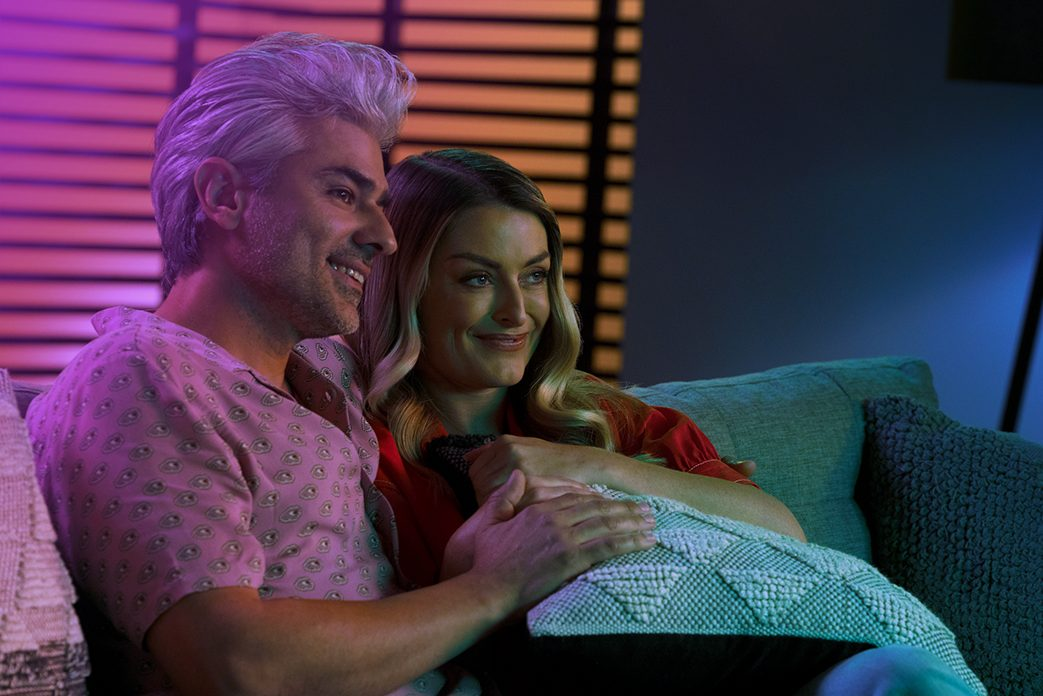 Image of a couple on a couch watch TV together