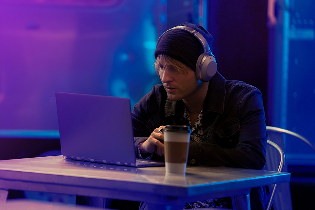 Image of man wearing headphones watching laptop