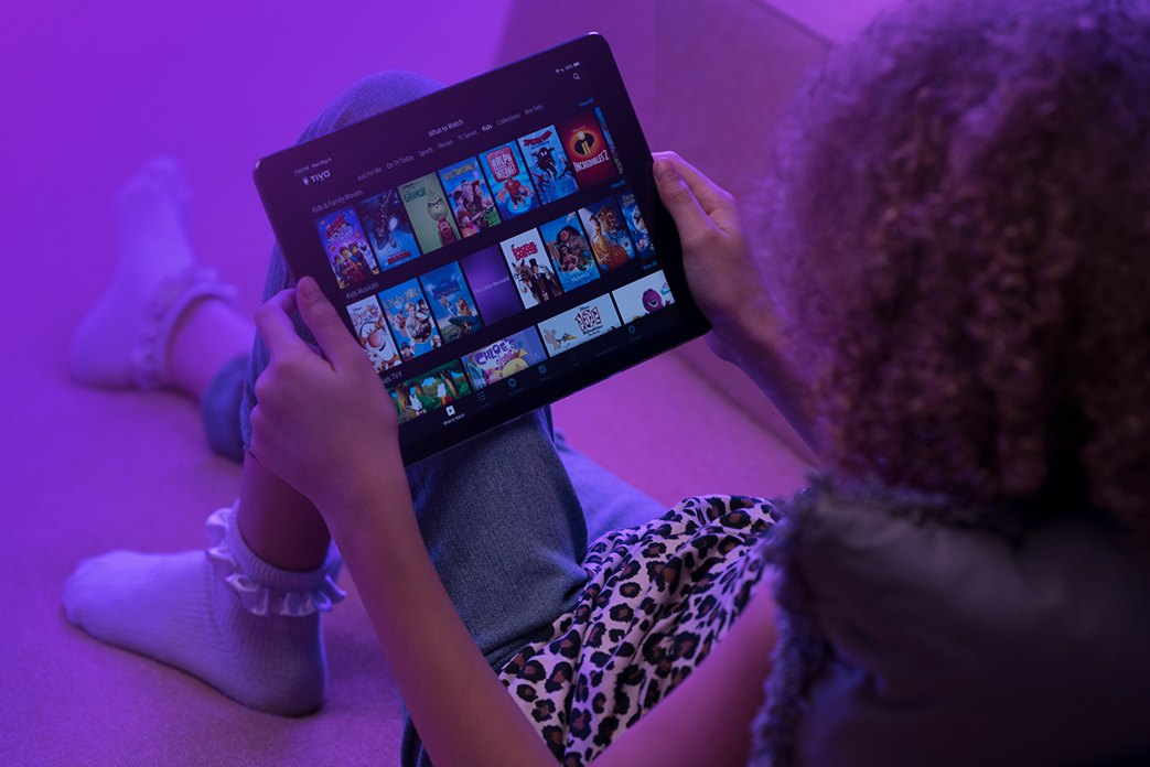 Image of an ipad held by a girl showing TiVo app