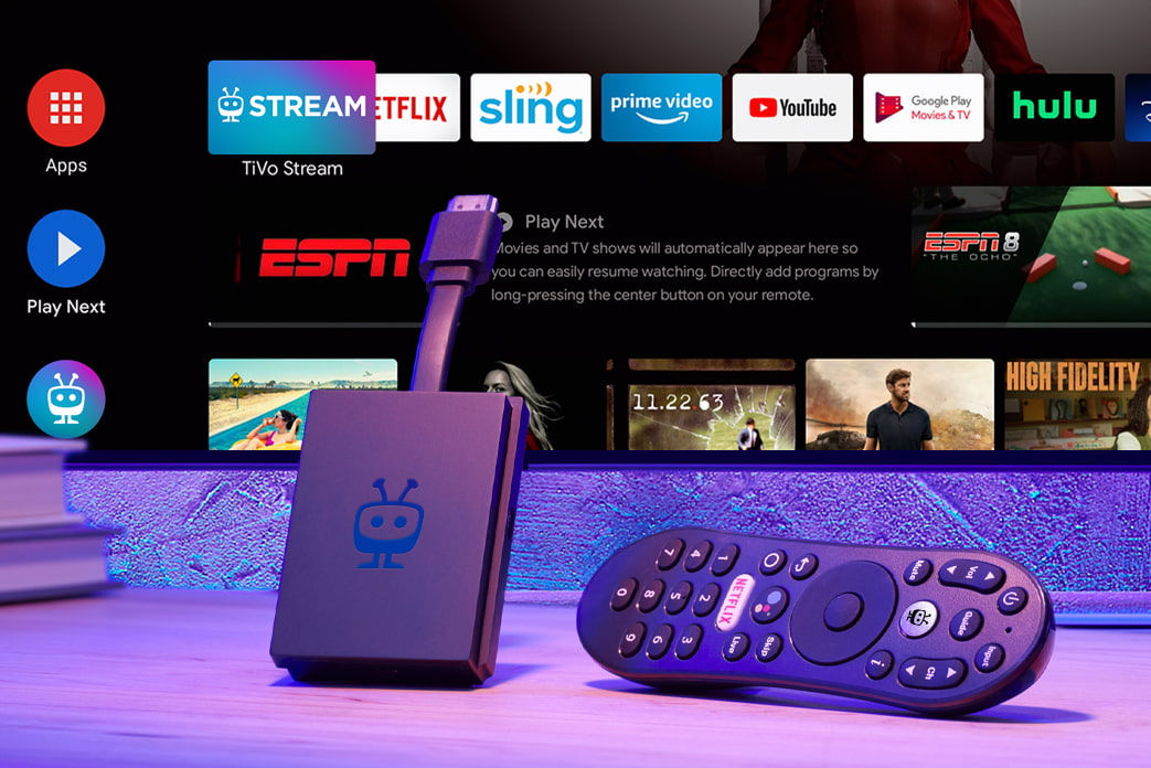 An image of the TiVo Stream 4K plus remote. A TV with the Stream 4K running hangs in the background.
