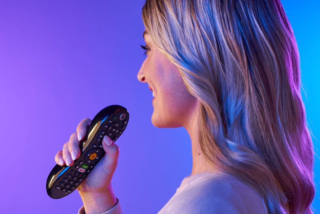 Image of a woman speaking into her TiVo Remote
