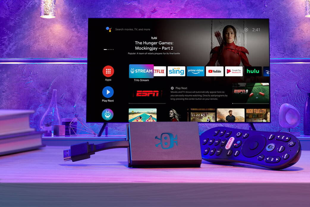 An image of the TiVo Stream 4K plus remote, sitting in front of a TV showing Android TV