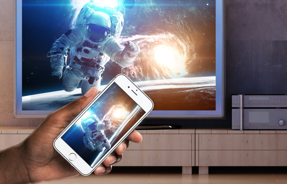 man holding phone in front of tv with an astronaut on it